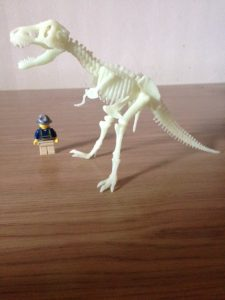 dinosaur skeleton about to eat up archaeologist lego man